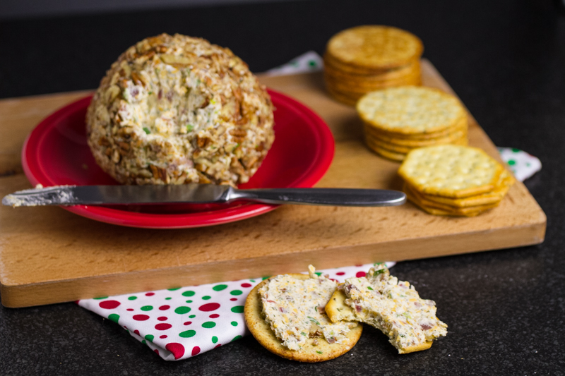 a photograph of a cheddar bacon ranch cheese ball on a plate with crackers in the background and crackers with cheese ball spread on them in the foreground