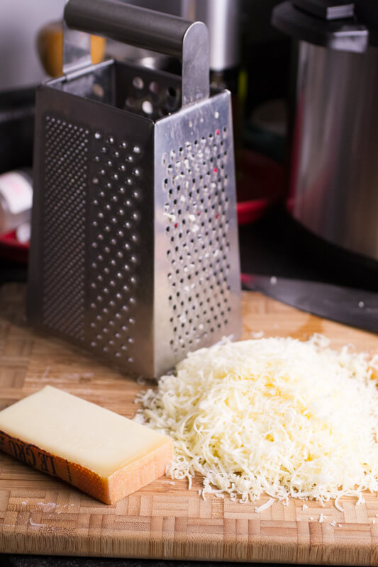 a photograph of a cheese garter and grated Gruyere cheese on a cutting board