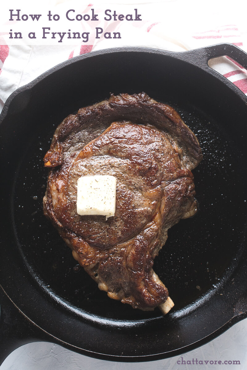 an overhead photograph of a pan-seared ribeye in a cast iron skillet with a pat of butter on top
