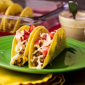 Baked cheeseburger tacos are stuffed with ground beef and cheese, baked, and topped with lettuce, tomato, and a classic burger sauce. | recipe from Chattavore.com