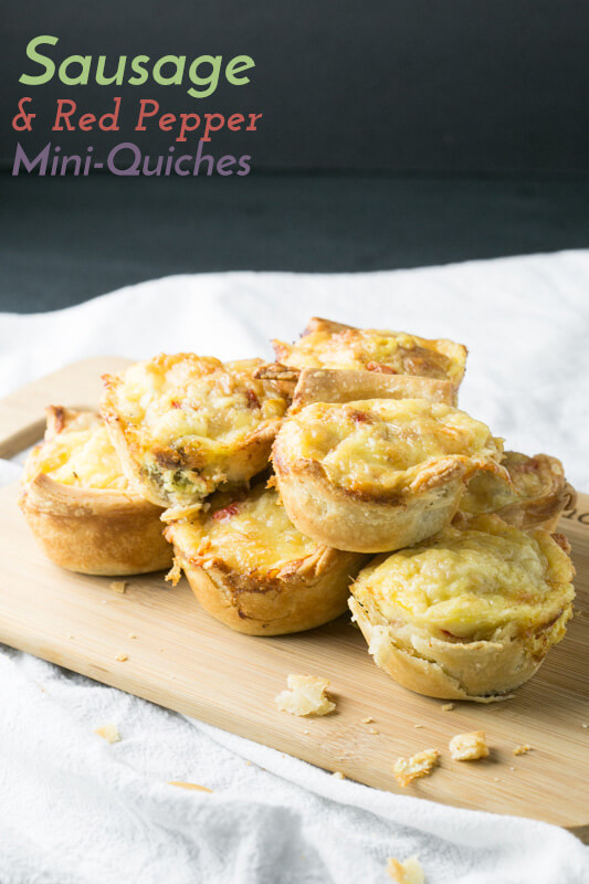 Sausage and red pepper mini-quiches stacked on a cutting board