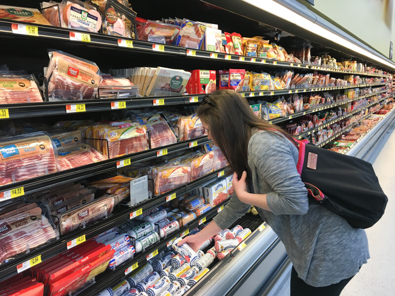 A photo of a woman getting a package of breakfast sausage from a cooler at a grocery store