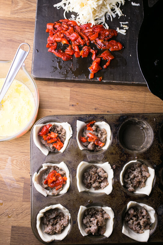 An overhead shot of a muffin pan filled with unbaked mini-quiches with sausage, a bowl of whisked eggs, and a cutting board with chopped roasted red peppers and grated cheese