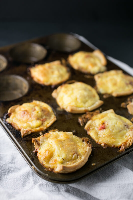 A picture of baked sausage and red pepper mini-quiches in a muffin tin