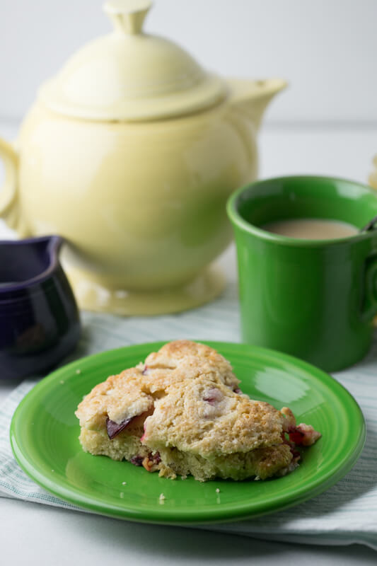 a picture of a scone with plums and Greek yogurt with a cup of tea, a teapot, and a pitcher of tea in the background
