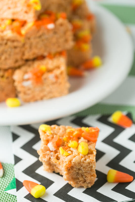 a candy corn Rice Krispies treat with a plate of candy corn Rice Krispies treats in the background
