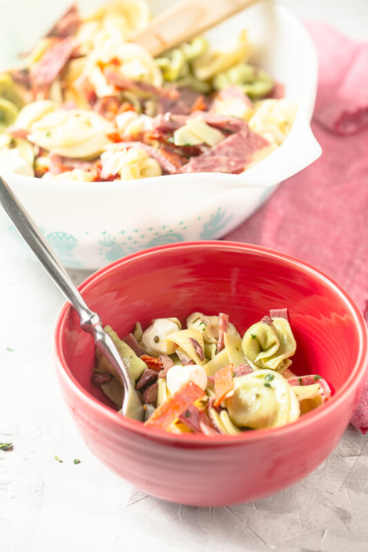 a small bowl of tortellini pasta salad with a larger bowl of tortellini pasta salad in the background
