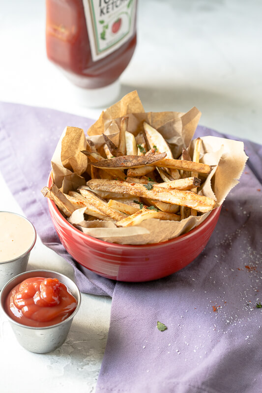 a photograph of a bowl of air fryer french fries with a cup of ketchup and a cup of dipping sauce beside it and a bottle of ketchup in the background