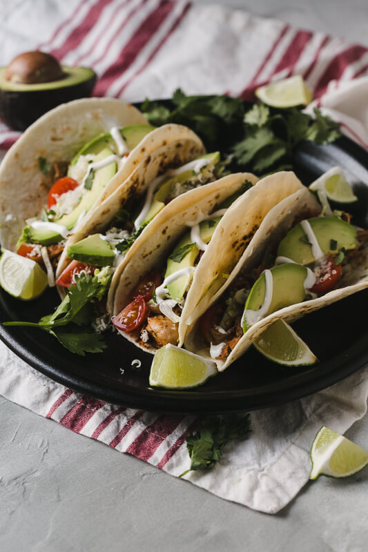 a photograph of a plate of Instant Pot chicken tacos with limes, avocado, and cilantro