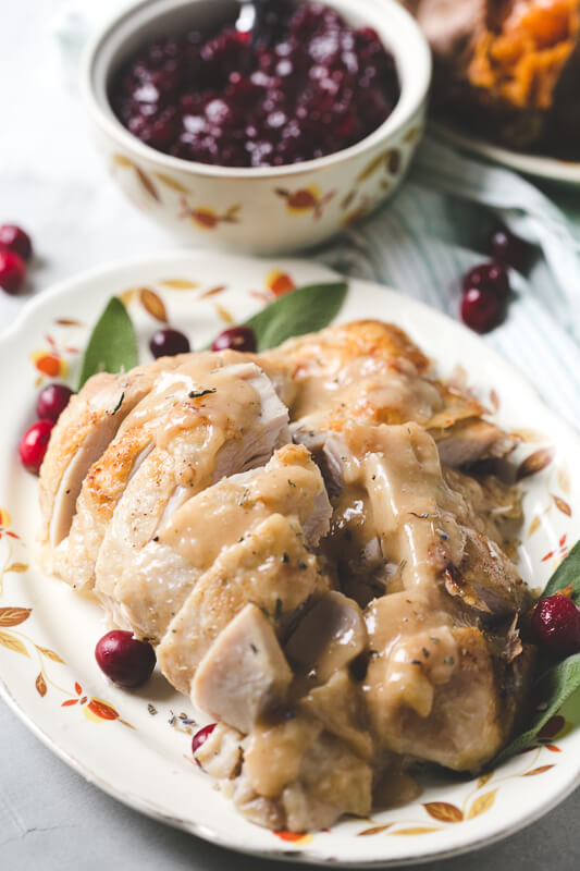 a close-up photograph of an Instant Pot turkey breast sliced and covered with gravy, with a bowl of cranberry sauce in the background