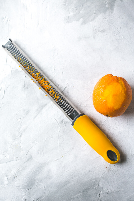 an overhead photograph of a zested orange and a zester with orange zest