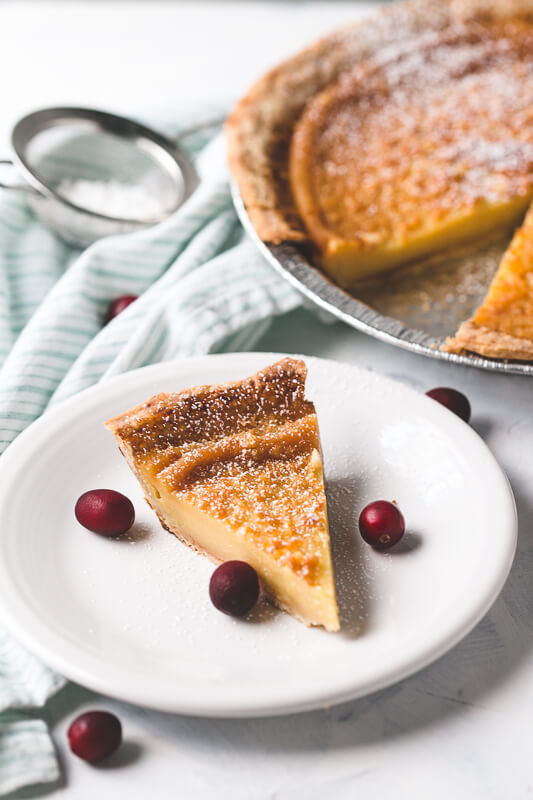 a slice of eggnog pie on a plate with a whole pie and a shaker of powdered sugar in the background