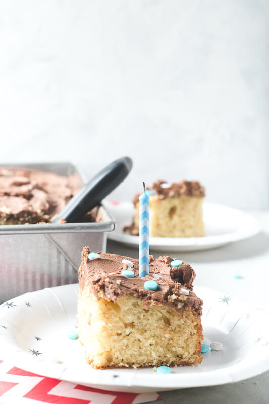 a slice of yellow cake from scratch with chocolate frosting on a plate with a blown-out candle, and a whole cake and another slice of cake in the background