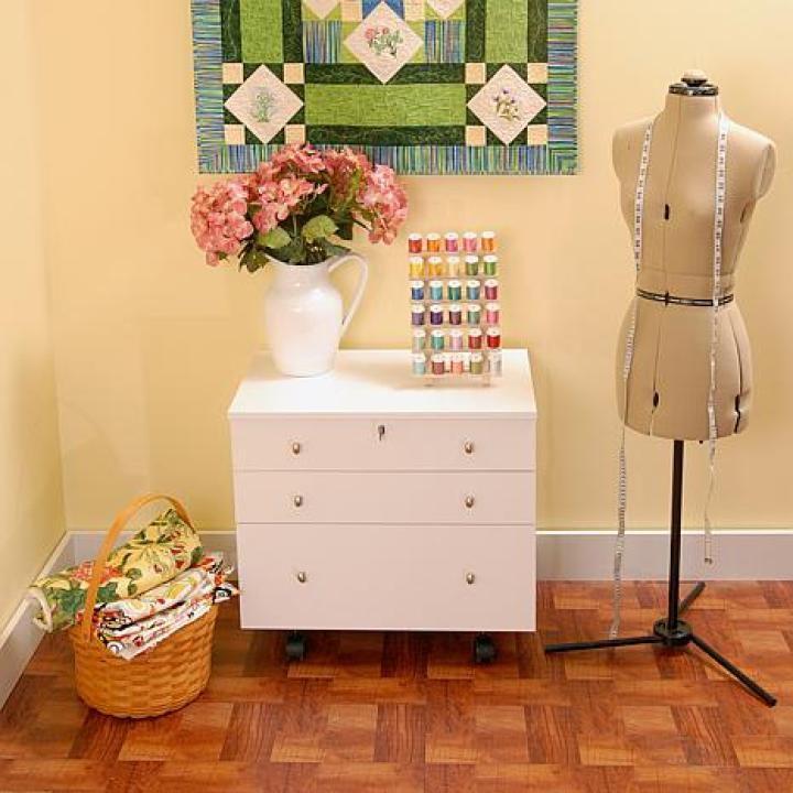 Is this cozy looking or what? A basket for your fabrics, drawers for organizing, a silhouette, flowers, a quilted wallhanging, and an organizer for threads. I adore the way this corner is laid out for some personal display inspiration. This is something I would like to do! Perfect and simple for even the tiniest of spaces dedicated to making crafts.