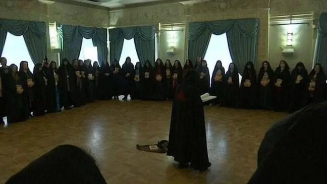 Reunidas em círculo, mulheres de capuzes e túnicas pretos, com um símbolo místico vermelho nas costas, fazem um ritual para ajudar o presidente da Rússia, Vladimir Putin.