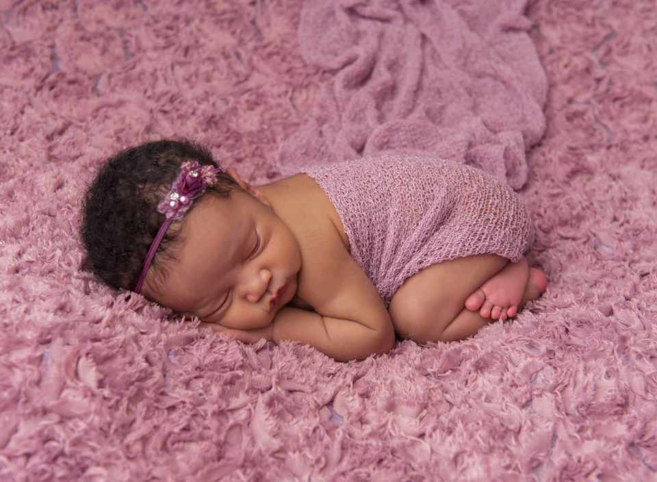sleeping newborn baby on purple blanket