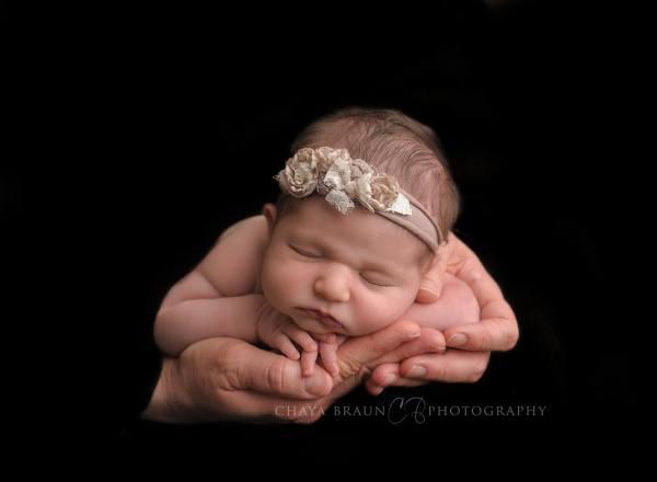 newborn baby girl in her Daddy's hands