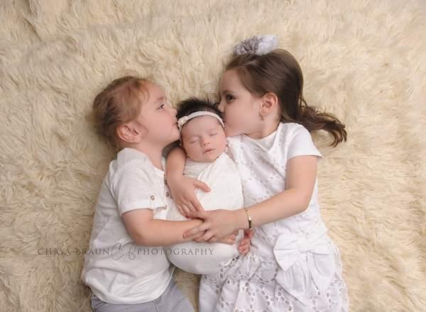 newborn and kissing siblings