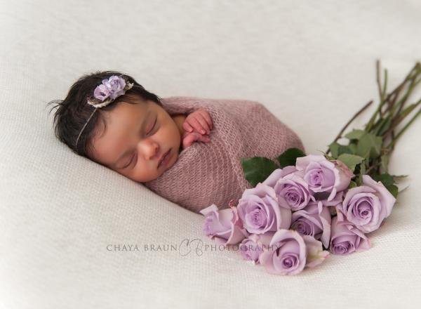 sleeping newborn baby with flowers