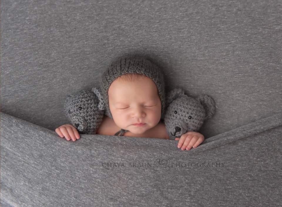 sleeping newborn baby with teddy bears