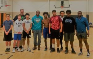 Group of teen boys standing with Chaz and Coach in a highschool gym posing for a picture Chaz Jackson will motivate and inspire your teens