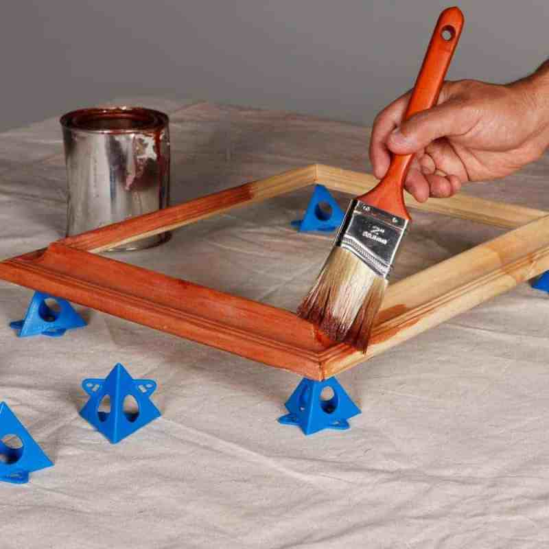 Paint pyramids hold cabinet doors in place to make staining easier.