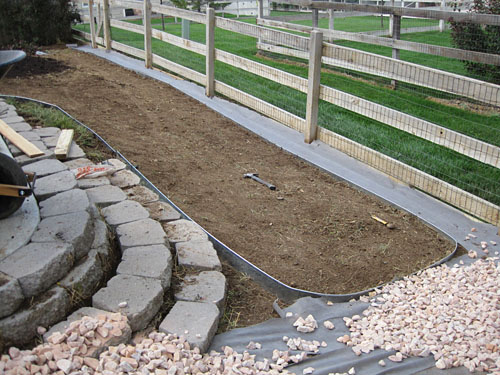 Backyard after installing some edging, fabric and spreading some rocks