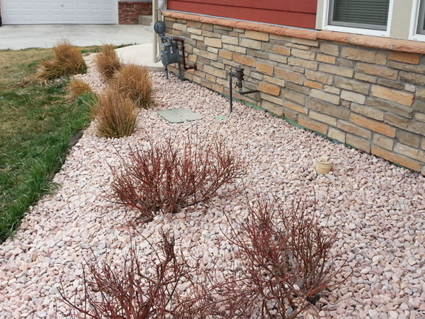 Landscape bed with river rock mulch around the house