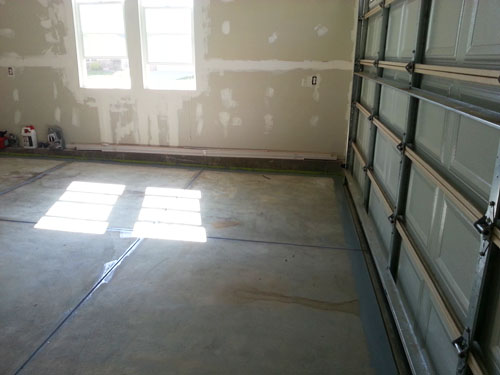 Trimmed garage floor edges and contraction joints as part of the process of applying an epoxy floor coating