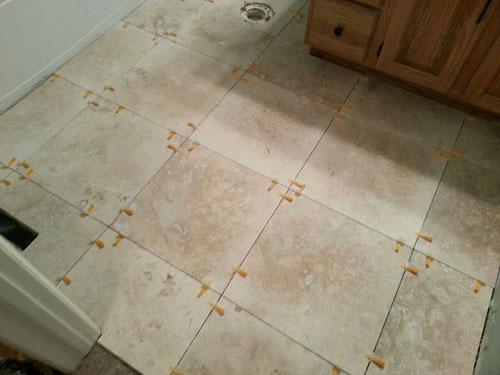 Travertine tile installed in the bathroom floors using tile spacers