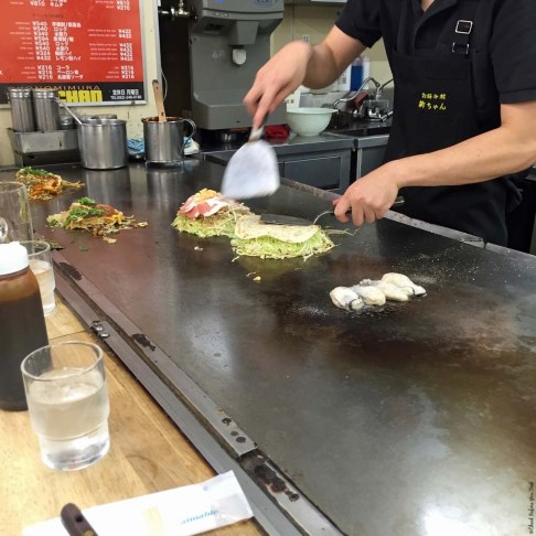 Step 4 in making Okonomiyaki at a food stall in Okonomimura - Hiroshima, Japan