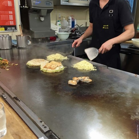 Step 5 in making Okonomiyaki at a food stall in Okonomimura - Hiroshima, Japan