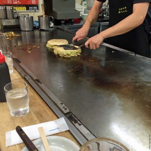 Step 6 in making Okonomiyaki at a food stall in Okonomimura - Hiroshima, Japan