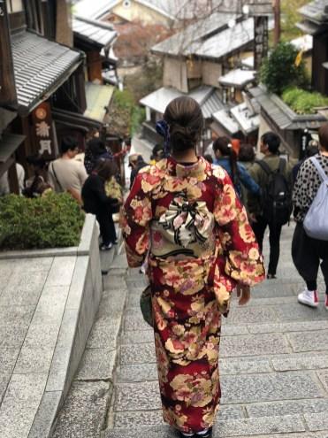 Walking down historic street in kimono.
