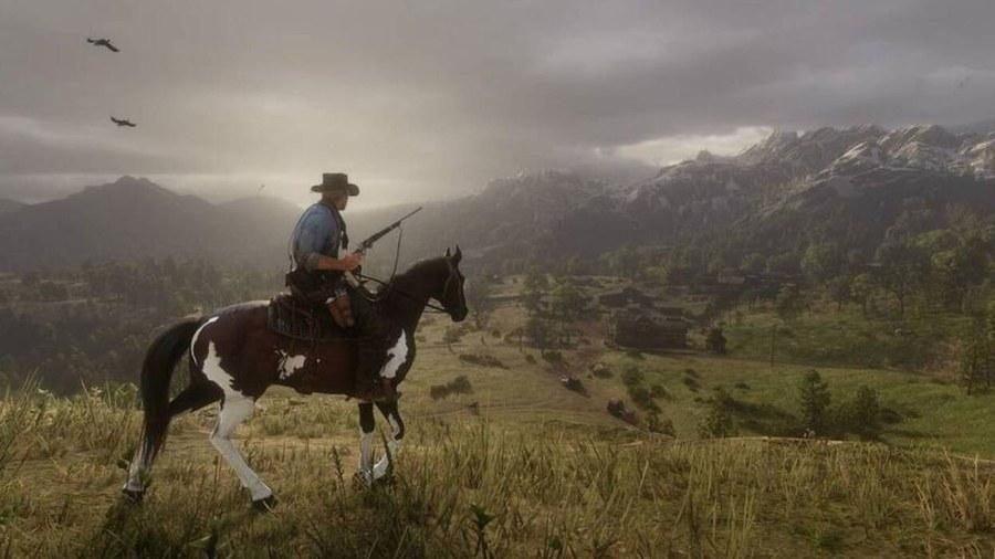 cowboy riding a horse on a hilltop