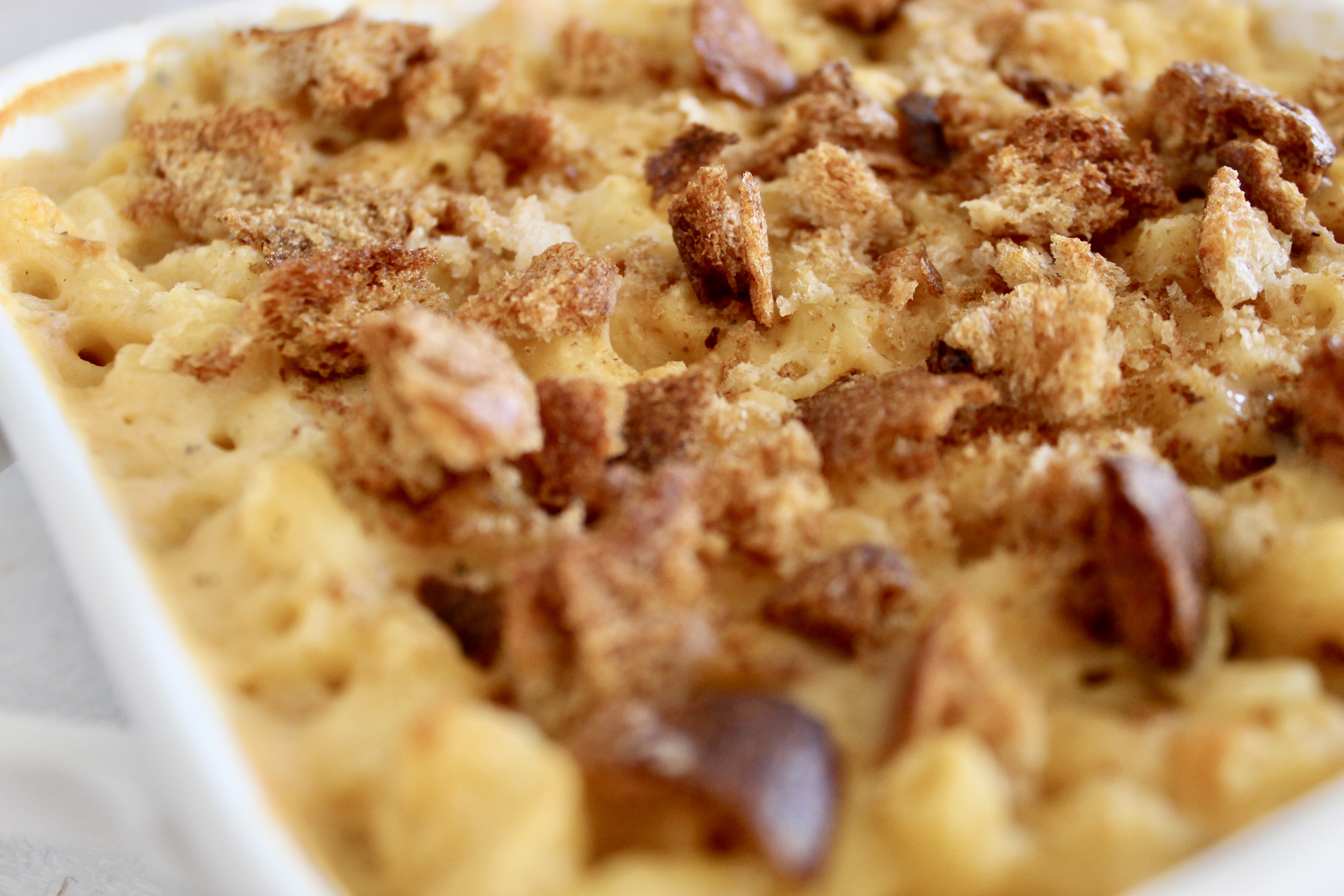 Sharp cheddar, muenster, and asiago makes for an indulgent, three cheese Homemade Breadcrumb Baked Mac and Cheese. Some simple healthy recipe swaps help reduce the fat, maintain the protein and increase the fiber content of this classic recipe.