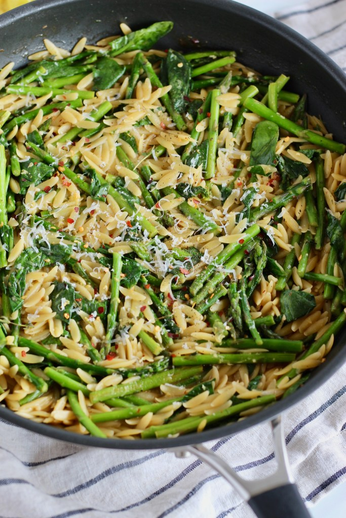 Close up of cooked asparagus and spinach over orzo