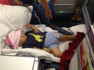 ▲日本時間では朝の4時ごろ。機内は電気がついていたものの、よく眠っていたので顔にタオルをかけていました。まだ顔は腫れていました。