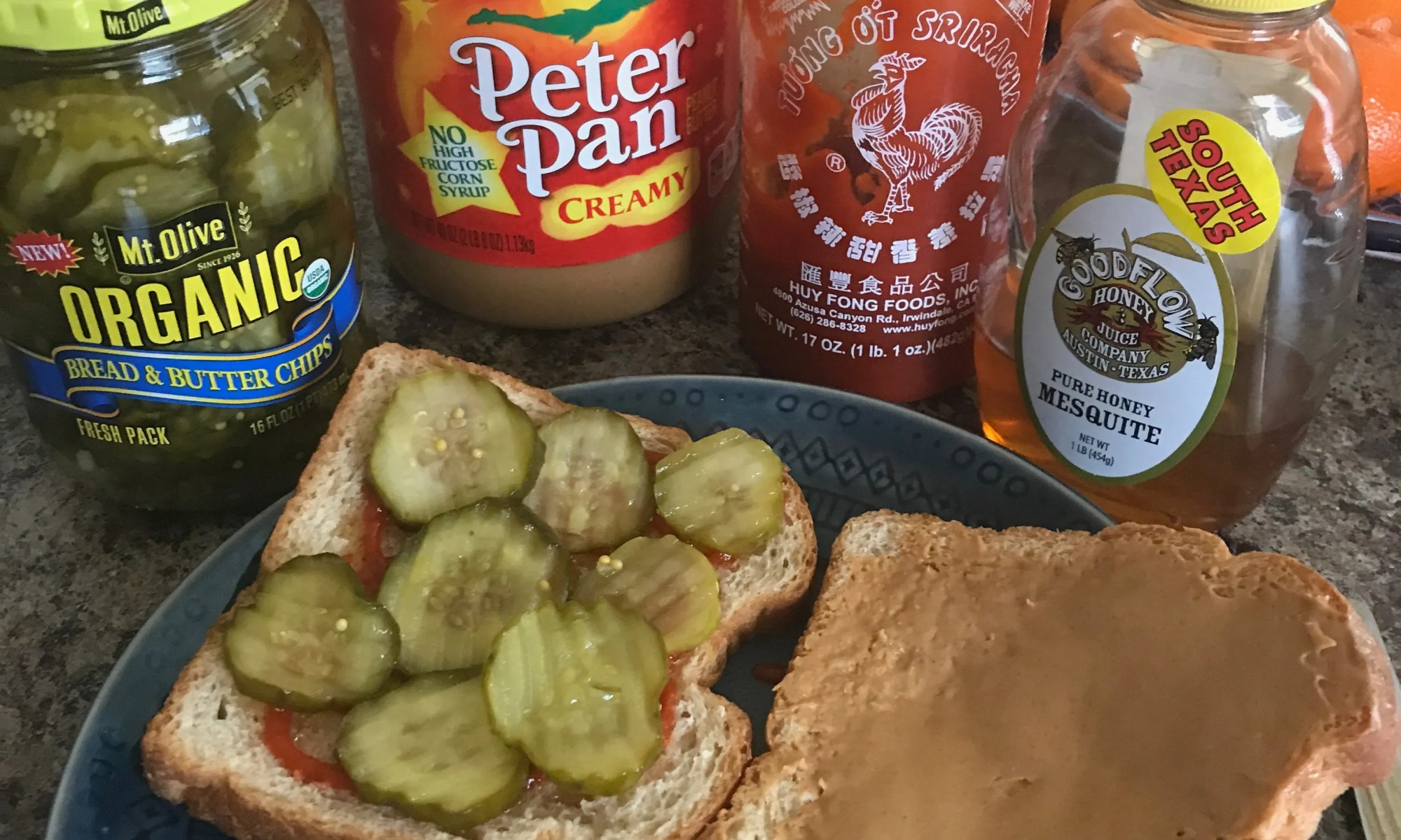 jar of bread n butter pickles, peanut butter, sirarcha, honey, two pieces of bread one spread with peanut butter the other pickles with honey and sirarcha on a blue plate.