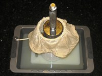 0.5 kg Gouda cheese pressing in homemade hoop and cloth bag shaped liner, expelled whey needs to be drained.