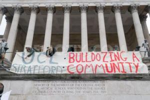 """Protesters against the proposed UCL campus in Stratford occupy the Portico with a banner reading """"UCL Stratford: bulldozing a community""""."""