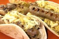 Grilled brats nestled in a warm flour tortilla, topped with sauerkraut, shredded Swiss cheese, and mustard.