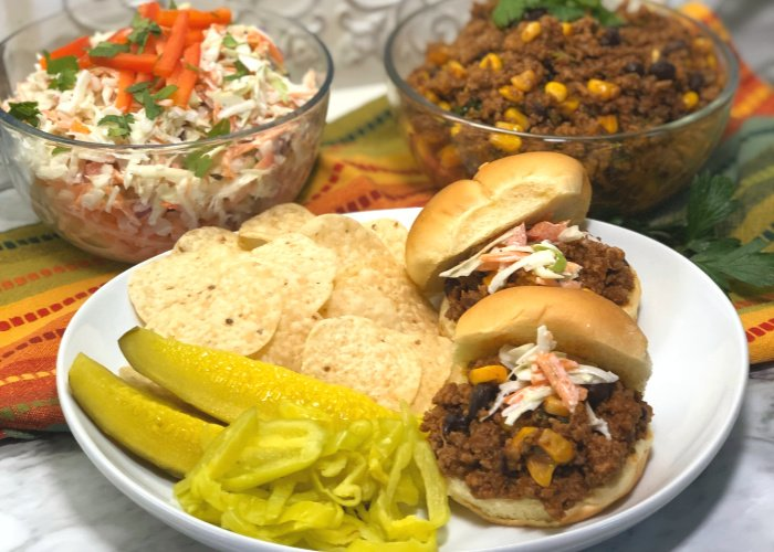 sloppy joes on a plate with chips and pickles