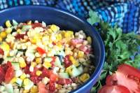 Corn salad with vegetables in a blue bowl.