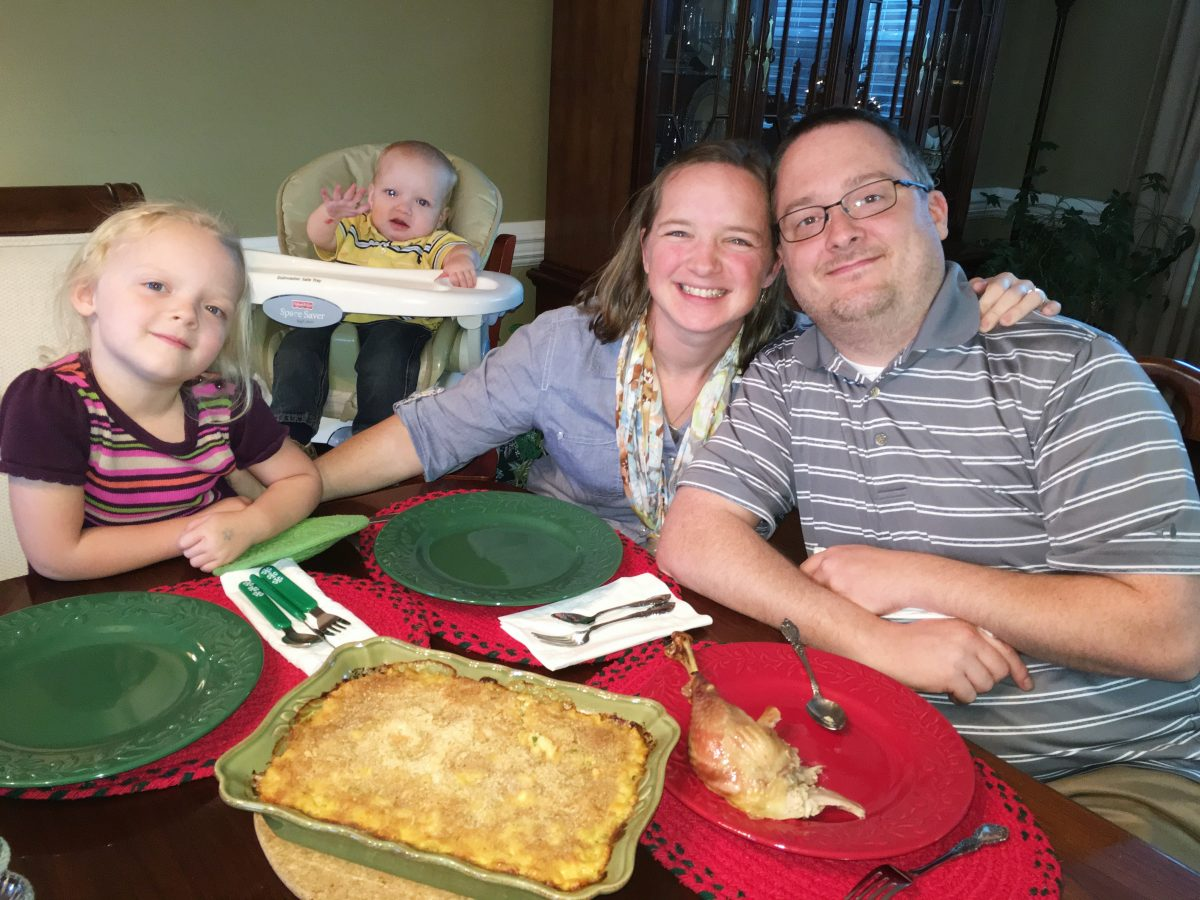 Family of four sitting at dinner table