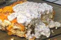 A piece of breakfast casserole with sausage gravy on top.