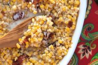 A creamy corn casserole topped with bacon and baked in a cast iron skillet or casserole dish.