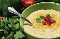 A bowl of tex mex soup with a spoon.