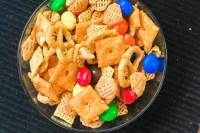 A bowl of party mix with candy.