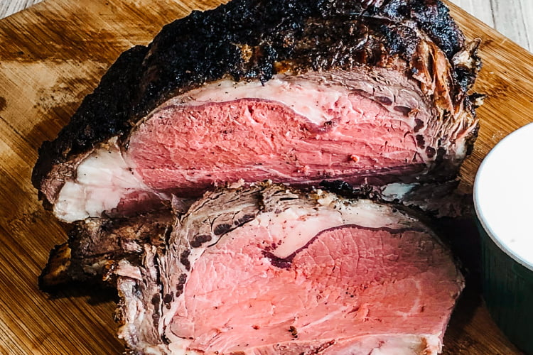 Prime rib roast with one slice laid on a cutting.